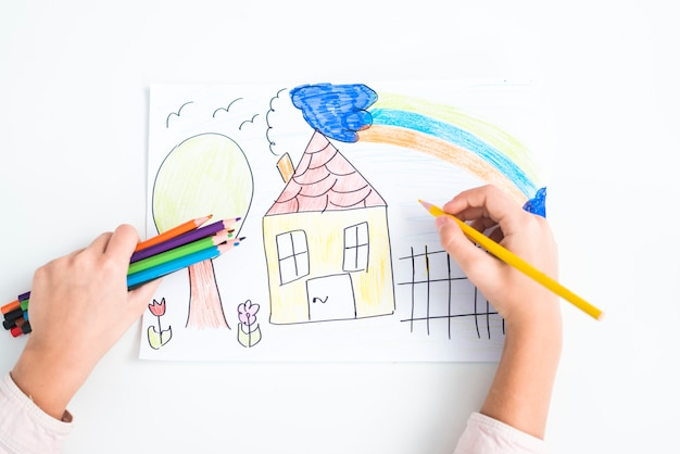 Close-up of girl's hand drawing the house with colored pencil on paper against white backdrop Premium Photo