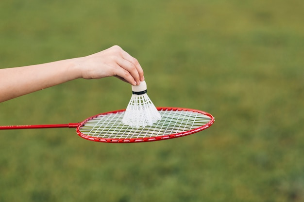Close-up of girl's hand placing shuttlecock over badminton Free Photo