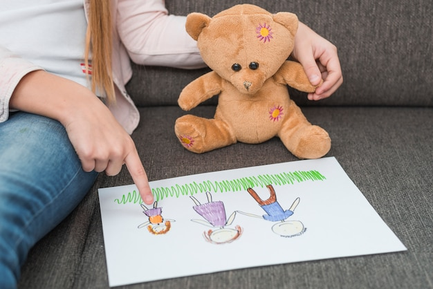 Close-up of a girl's hand showing family drawing made by her to teddy bear on sofa Free Photo