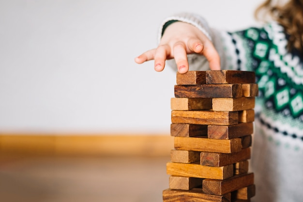 Close-up of a girl's hand stacking wooden blocks Free Photo