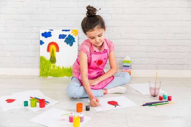 Close-up of a girl sitting on floor painting on white paper with paint Free Photo