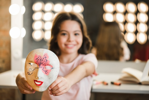 Close-up of a girl sitting in makeup room showing venetian mask Free Photo