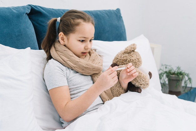 Close-up of a girl suffering from the cold and fever looking the temperature at thermometer Free Photo
