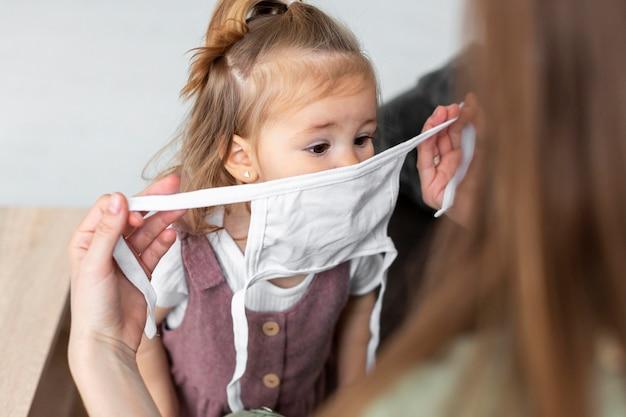 Maschera da portare della ragazza del primo piano Foto Gratuite
