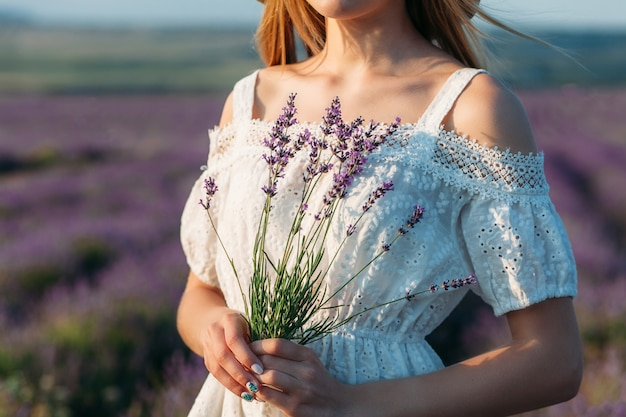 Close-up of a girl in a white dress holding a bouquet of lavender in her hands Premium Photo