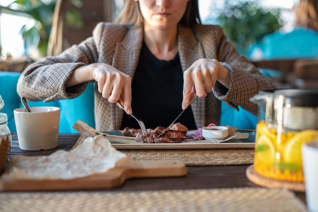 Close-up of girl with cutlery in restaurant eating roast meat Premium Photo