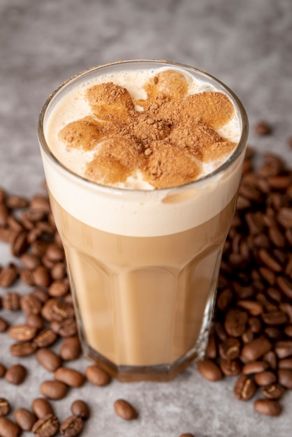 Close-up glass of cappucino with coffee beans Free Photo