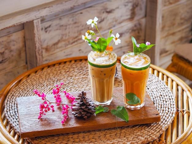 カフェで木製のヴィンテージテーブルに花の装飾とタイのミルクティーと冷たいコーヒーのガラスを閉じます。 Premium写真