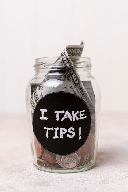 Close-up glass with money as tips Free Photo