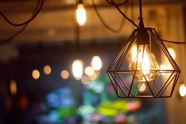 Close-up glowing hanging spherical retro vintage edison incandescent bulb against background of blurred other lamps Premium Photo