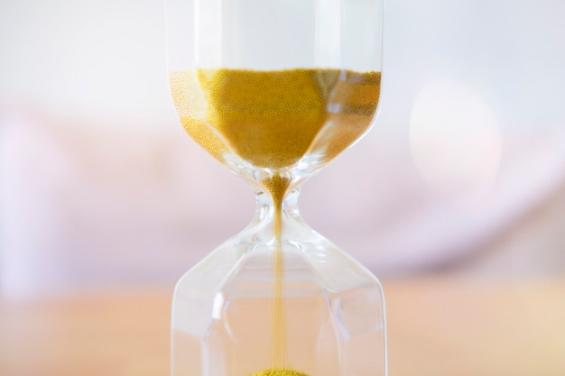 Close up gold sand running through the bulbs of an hourglass. Premium Photo