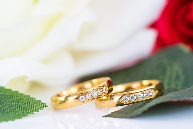 Close up of gold wedding rings and red rose Premium Photo