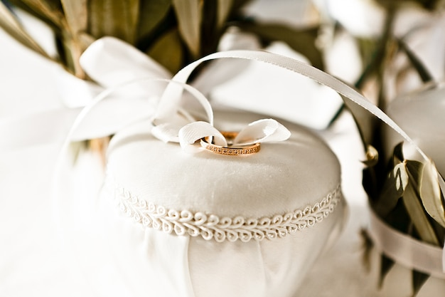 Close-up of gold wedding rings tied with a white silk ribbon to a jewelry box, selective focus Premium Photo