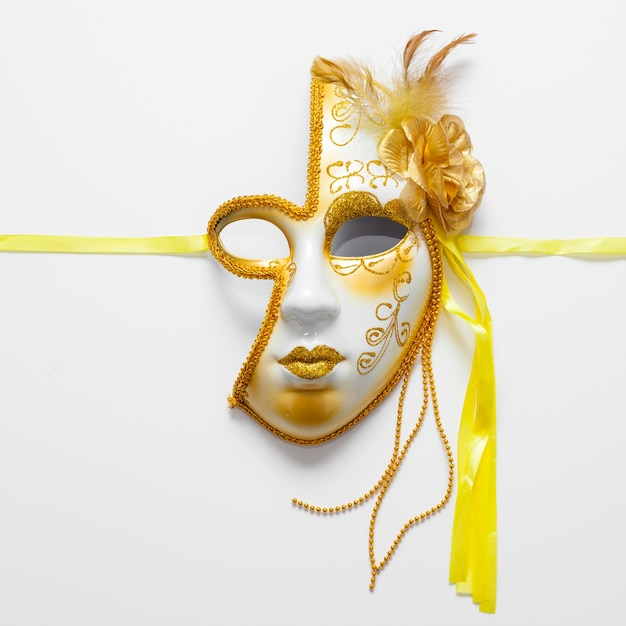 Close-up golden mask for carnival and yellow ribbons Free Photo