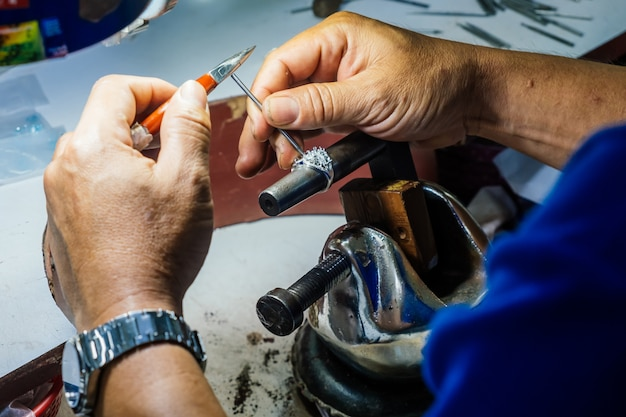 Close up of a goldsmith's hand making silver ring. Premium Photo