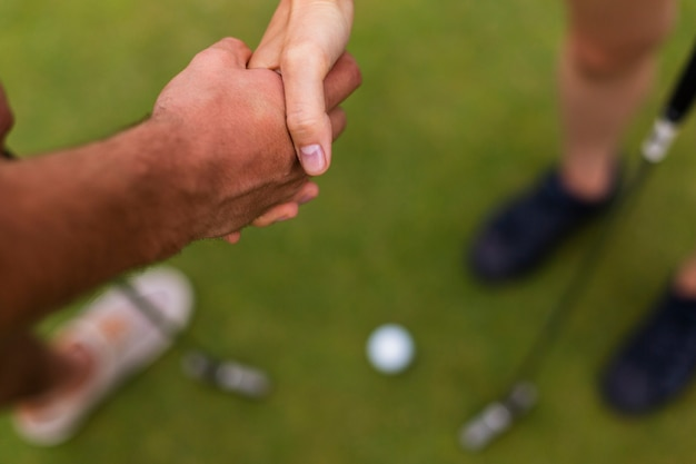Close-up golf players shaking hands Free Photo