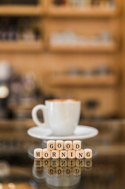 Close Up Of Good Morning Cubic Blocks With Cup Of Coffee On Glass