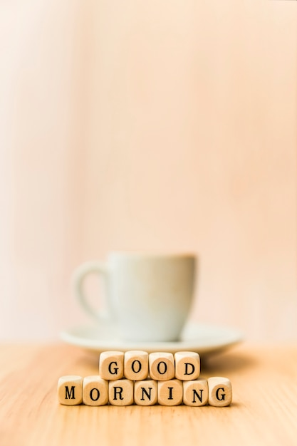 Close-up of good morning cubic blocks with cup of coffee on wooden surface Free Photo