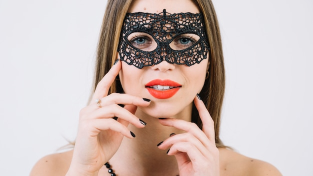 Close-up of a gorgeous smiling woman in black carnival mask Free Photo