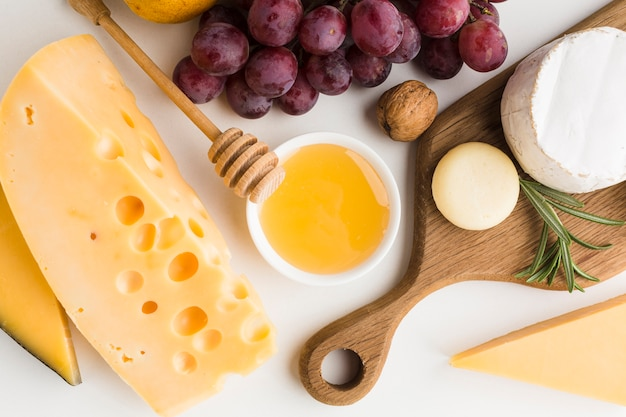 Close-up gourmet assortment of cheese on wooden cutting board and grapes Free Photo