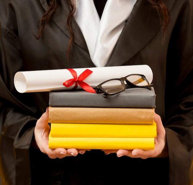 Close-up graduate student holding books Free Photo