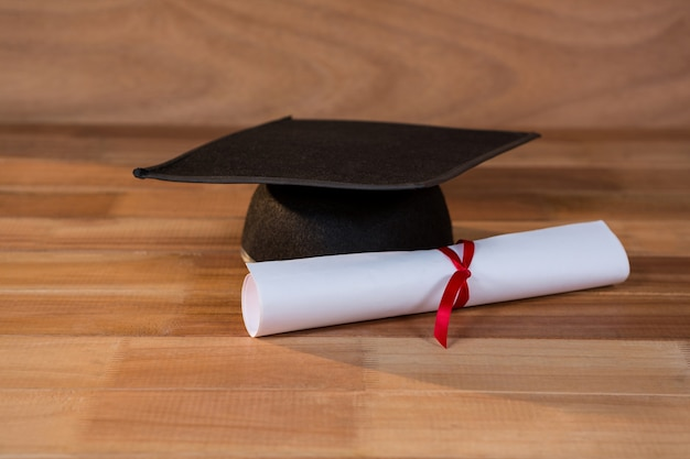 Close-up of graduation certificate with mortar board on a table Free Photo