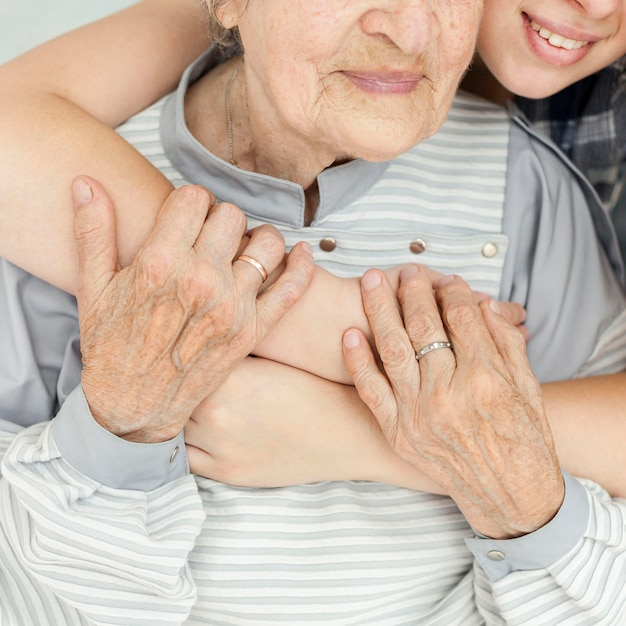 Close-up granddaughter hugging grandmother Free Photo
