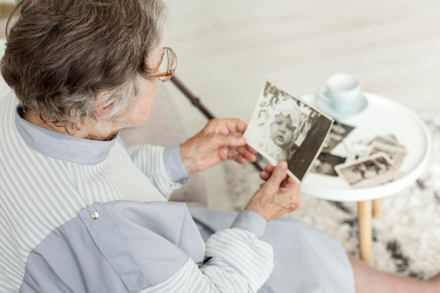 Close-up grandmother looking at old pictures Free Photo