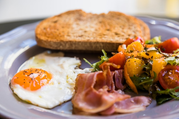 Close-up of gray plate with toast; fried eggs; bacon and salad Free Photo