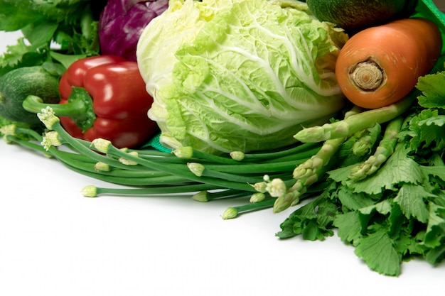 Close up a  green grocery bag of mixed organic green vegetables on white Premium Photo