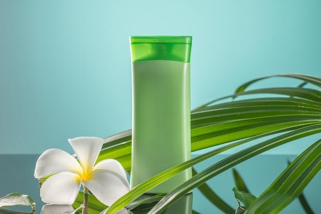 クローズアップ:緑の有機シャワージェルとプルメリアの花、緑の背景に緑の葉 Premium写真