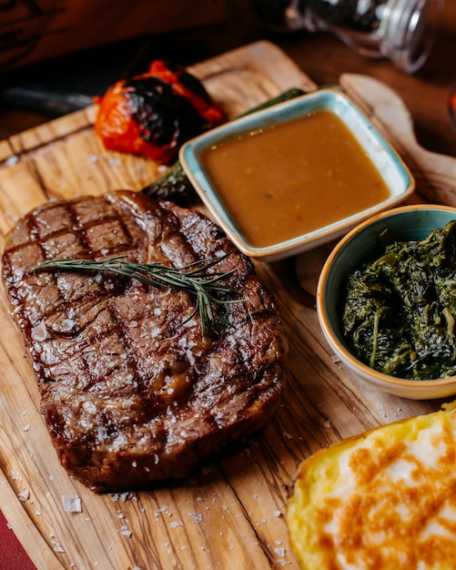 Close up of grilled beef steak with baked potato and sauce on a wooden board Free Photo