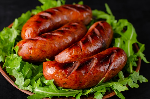 Close up of grilled sausages and arugula on black background. Premium Photo