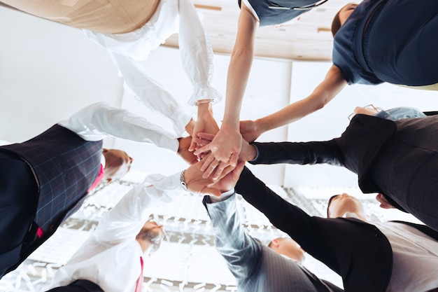 Close up of group of businesspeople putting their hands on top of each other Premium Photo
