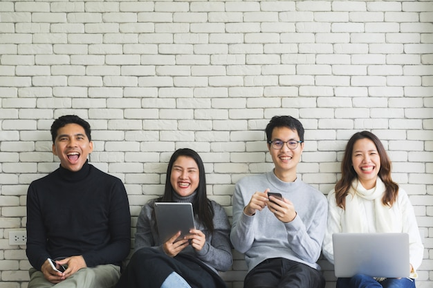 Close up group of millennial generation holding modern gadget devices and sitting on white wall room Premium Photo