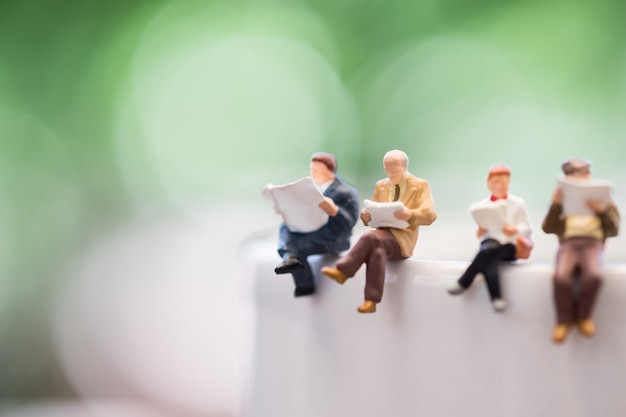 Close up of group miniature mini figures man and woman sit and read a book and a newspaper on cup Premium Photo