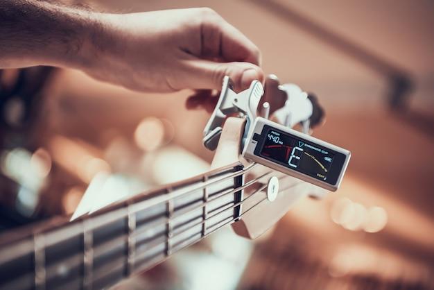 Close up. guitarist tunes guitar with tuner clip. Premium Photo