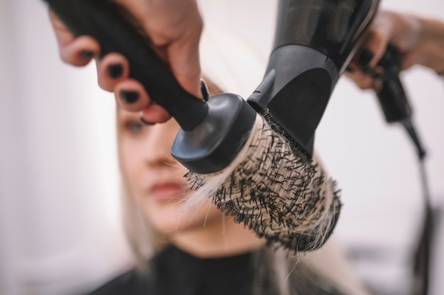 Close-up of hair styling with brush Free Photo