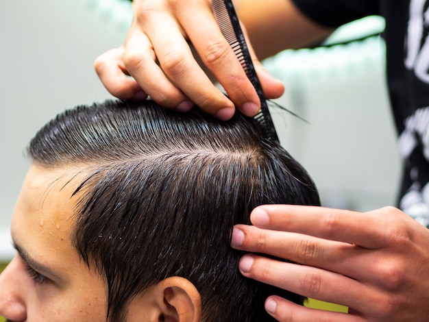 Close-up hairdresser combing hair Free Photo