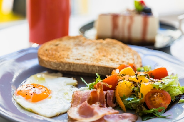 Close-up of half fried egg; bacon; salad and toast on gray ceramic plate Free Photo