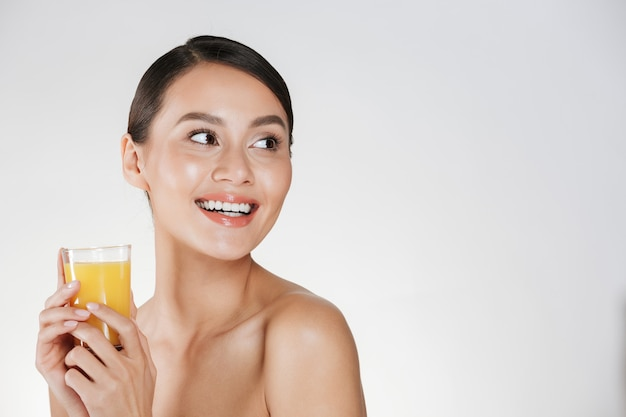 Close up of half-naked gentle woman with healthy fresh skin looking away and holding orange juice from transparent glass, isolated over white wall Free Photo