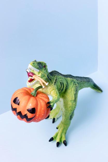 Zucca della tenuta del giocattolo del dinosauro di halloween del primo piano Foto Gratuite