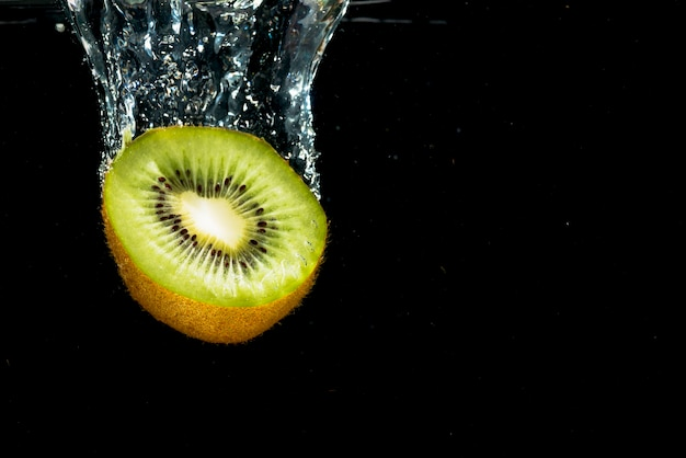 Close-up of halved kiwi falling with water splash Free Photo