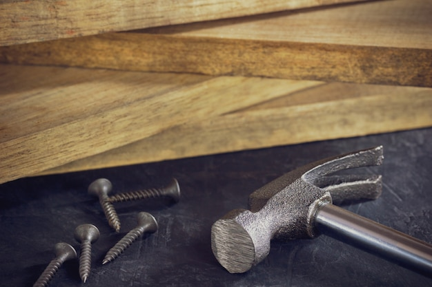 Close up hammer and screw in lumber stacking. copy space. concept of carpenter or construct. Premium Photo