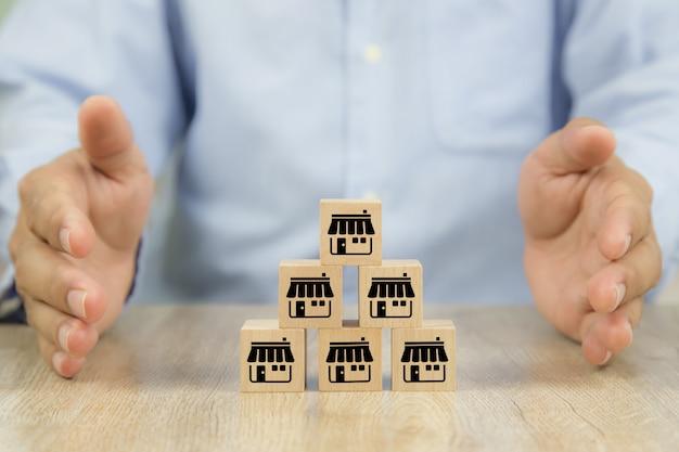 Блоки игрушки руки и куба конца-вверх деревянные штабелированные в пирамиде с значком магазина дела франшизы. Premium Фотографии