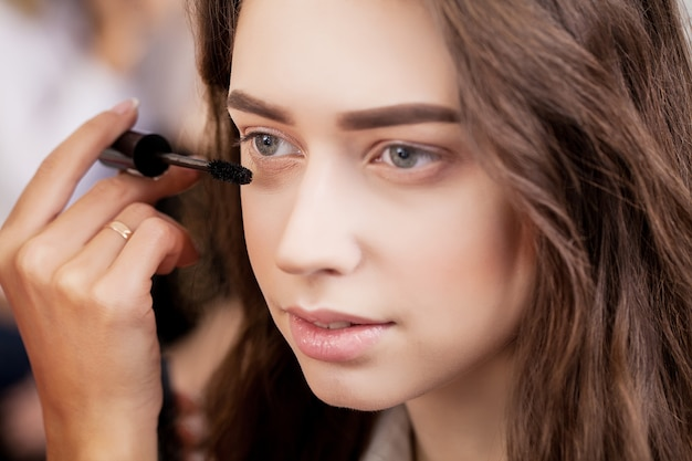 Close up of hand of asian woman applying eyeshadow on female eyelid. Premium Photo
