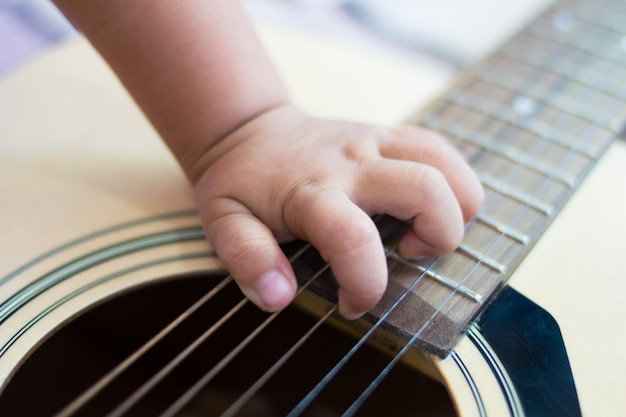 Close up hand baby playing the guitar Photo | Premium Download