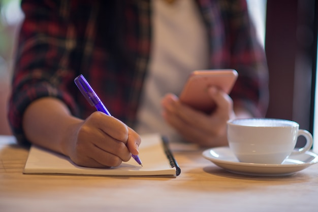 Close up hand beautiful woman writing notebook with coffee cup in coffee shop Premium Photo