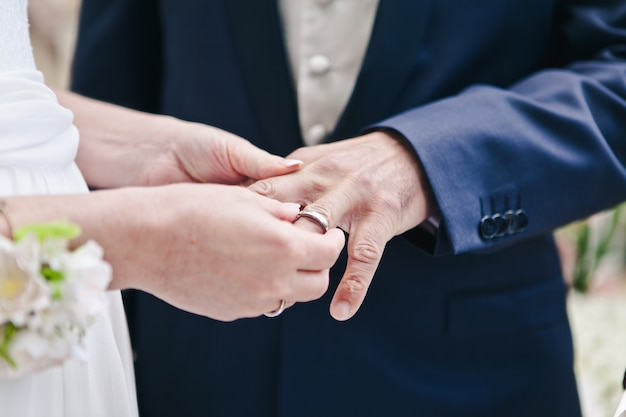 Close-up of the hand of the bride puts a wedding ring on the grooms finger, the ceremony on the street Premium Photo