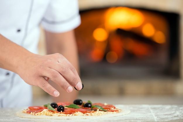 Close-up. hand of chef baker in white uniform making pizza. Premium Photo